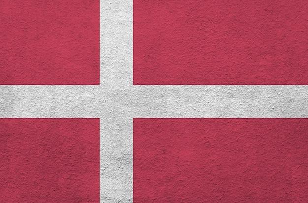 Dänemark flagge in hellen farben auf alten reliefputzwand dargestellt. strukturiertes banner auf rauem hintergrund