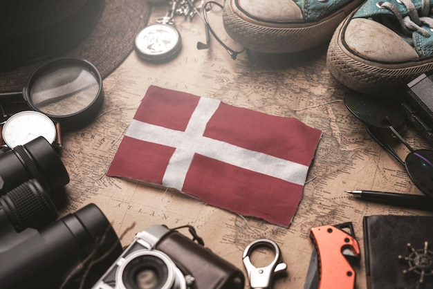 Dänemark-flagge zwischen dem zubehör des reisenden auf alter weinlese-karte. touristisches bestimmungsort-konzept.