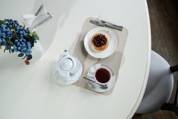 Dänischer kuchen mit kirschen und schwarzem tee auf einem tisch in einem gemütlichen café