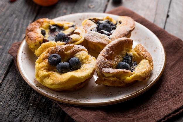 Dänischer pfannkuchen mit beeren, die mit zuckerpulver bedeckt sind