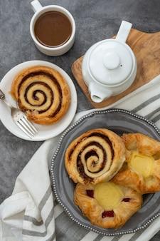 Dänisches gebäck mit kaffeetasse zum frühstück. zimtschneckenbrötchen.