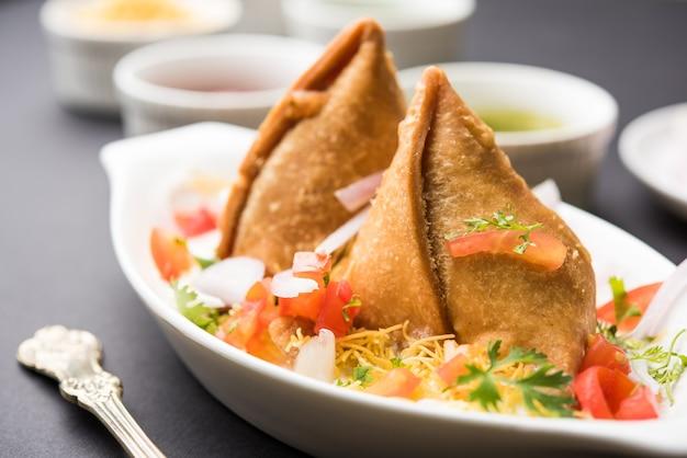 Dahi samosa oder samosa ist ein beliebter nordindischer snack, der in quark getaucht wird Premium Fotos