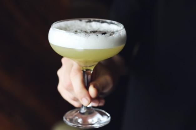 Daiquiri-cocktail in der weiblichen hand auf schwarzem hintergrund