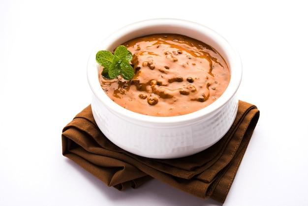 Dal makhani oder daal makhni ist ein beliebtes essen aus punjab, indien, das aus ganzen schwarzen linsen, roten kidneybohnen, butter und sahne hergestellt und mit knoblauch-naan oder indischem brot oder roti . serviert wird