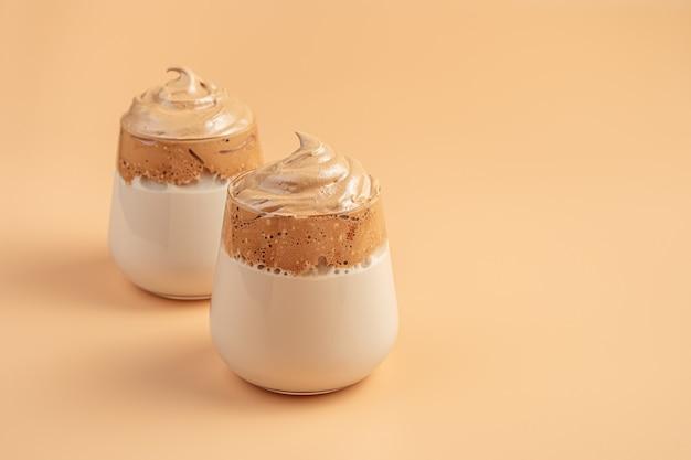 Dalgona-kaffee an einer orangefarbenen wand. geschlagener kaffeeschaum und milch. seitenansicht, kopienraum.