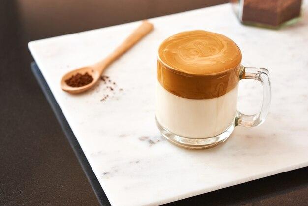Dalgona kaffee flauschig cremig shake kaffee in einem transparenten glas auf einer marmoroberfläche neben einem holzlöffel