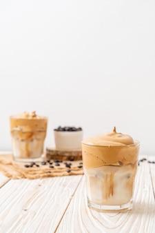 Dalgona kaffee. gefrorenes, cremiges, geschlagenes trendgetränk mit kaffeeschaum und milch