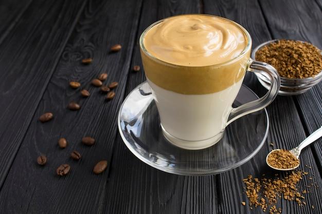 Dalgona-kaffee in der glasschale auf schwarzem holz. nahansicht.