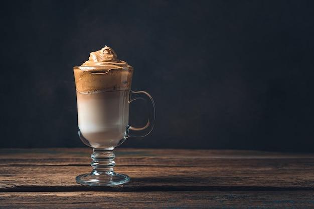 Dalgona-kaffee in einem hohen klaren glas an einer braun getönten wand. seitenansicht, kopienraum.
