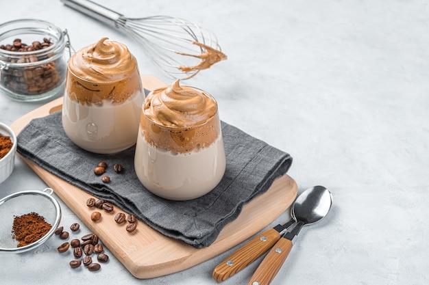 Dalgona-kaffee in klaren gläsern an einer grauen wand. koreanisches belebendes getränk. platz kopieren.
