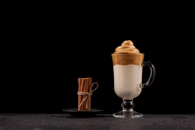 Dalgona-kaffee mit einem dicken schönen schaum in hochtransparenter tasse auf steinerner nasser arbeitsplatte.