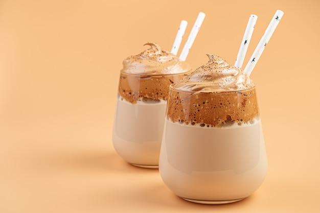 Dalgona-kaffee-nahaufnahme in zwei klaren gläsern mit strohhalmen an einer orangefarbenen wand