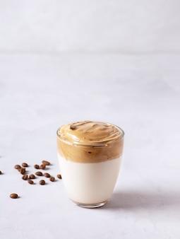 Dalgona kaffee steht in einem glas auf einem grauen betontisch