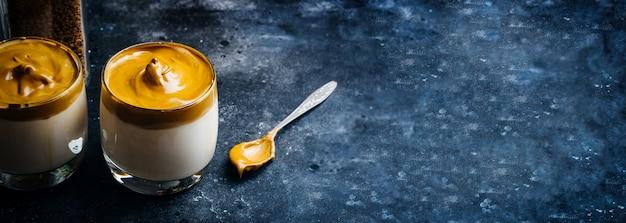 Dalgona kaffeegetränk hintergrund. koreanisches kaffeegetränk aus geschlagenem instantkaffee, zucker und milch.