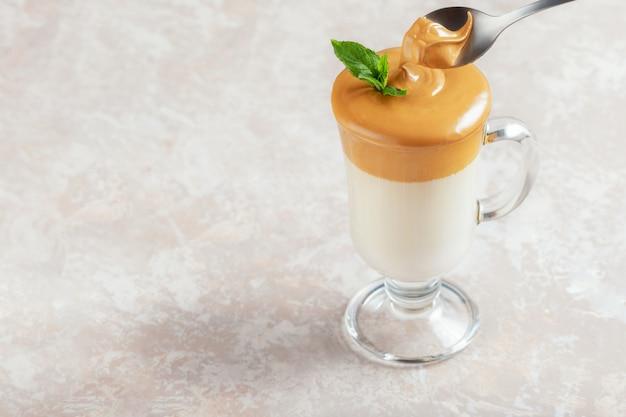 Dalgona schaumiger kaffee im glas auf hellem hintergrund. trend koreanisches iced latte kaffeegetränk mit schaum von instantkaffee mit kopierraum für text.