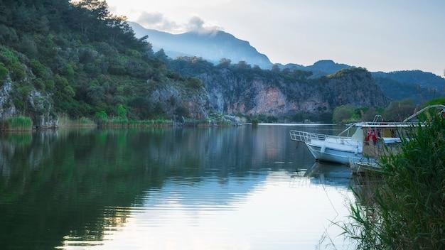 Dalyan-fluss mit boot und felsen bei sonnenuntergang im frühjahr. provinz mugla türkei