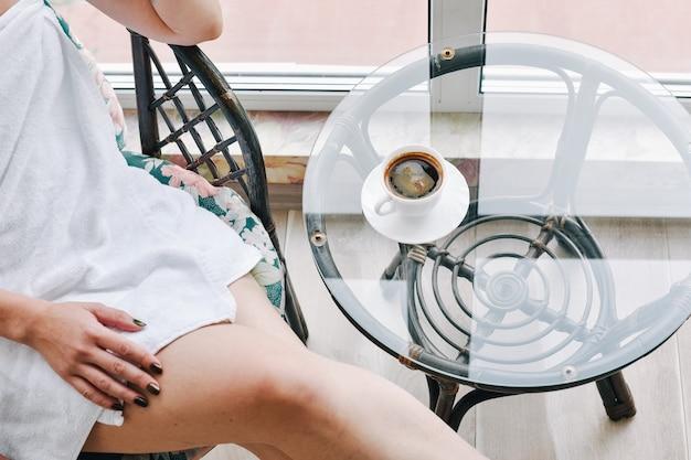Dame auf balkon mit morgenkaffee und weißem handtuch. mädchen in einem weißen handtuch trinkt kaffee