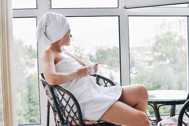 Dame auf dem balkon mit morgenkaffee und weißem handtuch auf den haaren. mädchen in einem weißen handtuch trinkt kaffee