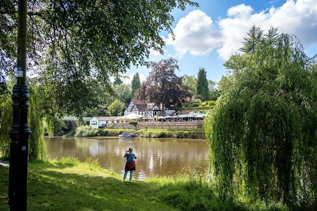 Dame beim fotografieren am fluss severn in shrewsbury, shropshire, england