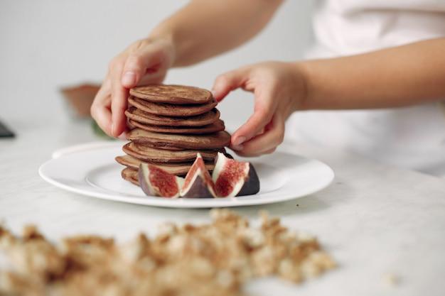 Dame bereitet dessert vor. konditor backt pfannkuchen.