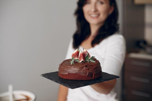 Dame bereitet nachtisch vor. frau backt einen kuchen. konditor mit schokoladenkuchen.