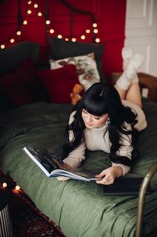 Dame, die auf einem bett ruht, mit lichterketten geschmückt, und ein buch in ihren händen betrachtend.