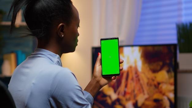 Dame, die auf greenscreen-smartphone schaut, während sie sich zu hause auf dem sofa entspannt. frau mit einem handy mit mockup-vorlage chroma-key isolierte handy-anzeige mit technologie-internet