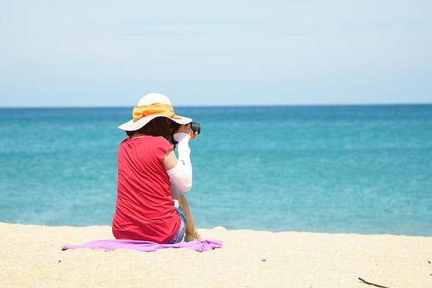 Dame, die auf strand sitzt und foto macht, sonnenschutzanzug kleidend