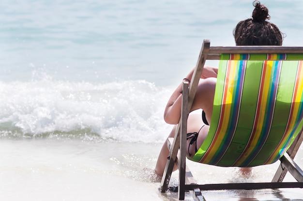 Dame, die auf strand sitzt und liest, entspannen sich bank auf schönem weißem sandstrand