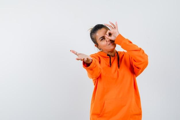 Dame, die ein okay-zeichen auf dem auge zeigt, die hand in einem orangefarbenen hoodie streckt und fröhlich aussieht