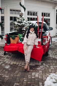 Dame, die einen kurzen pelzmantel trägt, der auf der kante einer roten lkw-karosserie mit weihnachtsbäumen und skiern ruht.