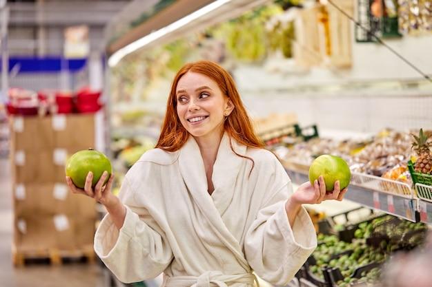 Dame, die frisches obst im lebensmittelgeschäft wählt, frau im bademantel genießt das einkaufen allein, steht im gang