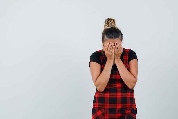 Dame, die gesicht mit händen im trägerkleid bedeckt und deprimiert aussieht, vorderansicht.