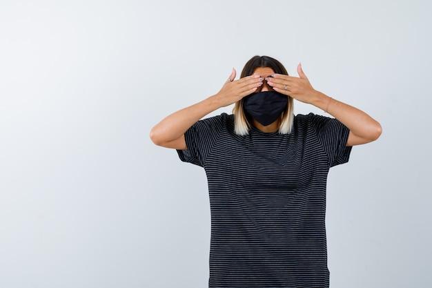 Dame, die hände auf augen im schwarzen kleid, in der medizinischen maske hält und aufgeregt schaut, vorderansicht.