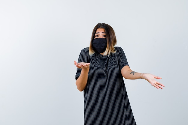 Dame, die hilflose geste im schwarzen kleid, in der medizinischen maske zeigt und verwirrt, vorderansicht schaut.
