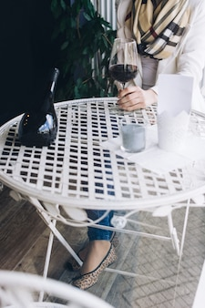 Dame, die ihr glas rotwein in einer weinhandlung trinkt