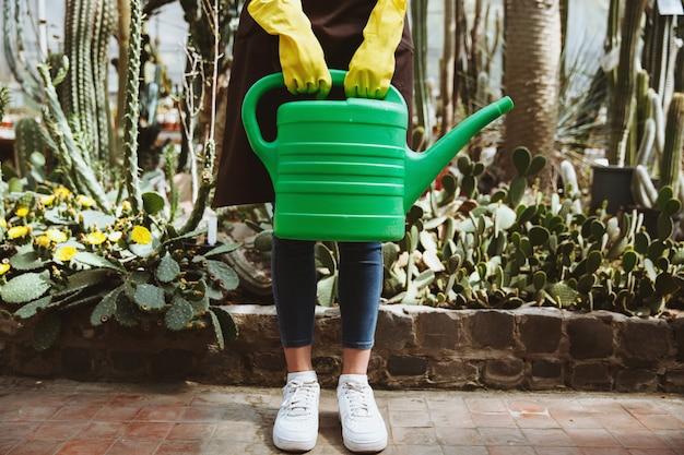 Dame, die im gewächshaus nahe pflanzen mit handgießtopf steht.