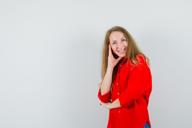 Dame, die in der denkenden haltung im roten hemd steht und fröhlich schaut.