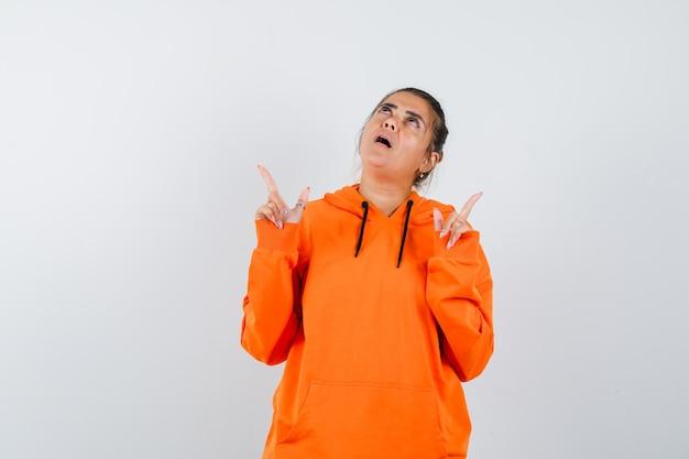 Dame, die in orangefarbenem hoodie nach oben zeigt und überrascht aussieht