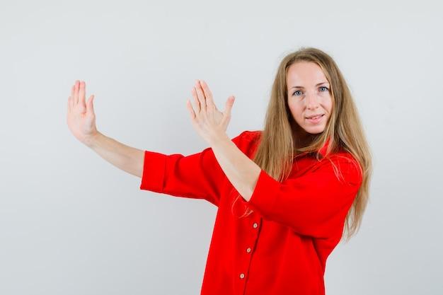 Dame, die karate-hieb-geste im roten hemd zeigt und zuversichtlich schaut,