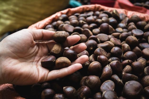 Dame, die kastanien an einem vietnamesischen landwirtmarkt auswählt