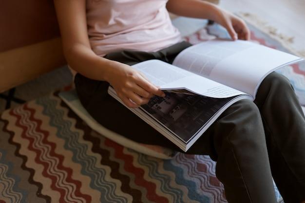 Dame, die mit farbigem teppich im zimmer sitzt und sein neues lieblingsmagazin über kunst genießt, blättert durch die seiten.