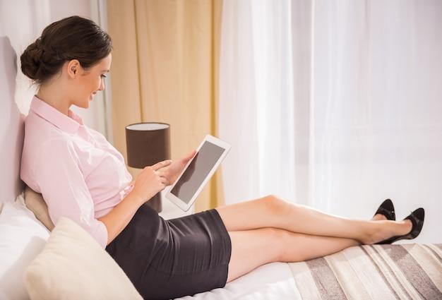 Dame, die mit ihrer digitalen tablette arbeitet und auf bett liegt.