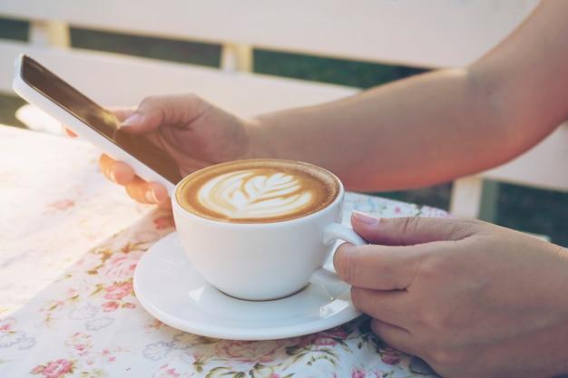 Dame, die mobilen weißen trinkenden kaffee verwendet