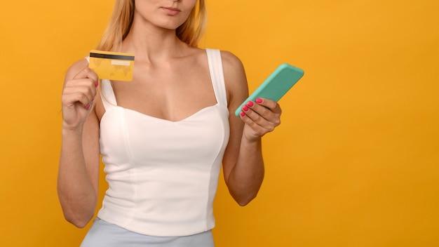 Dame, die online mit einer kreditkarte und einem smartphone auf gelbem hintergrund - bild kauft