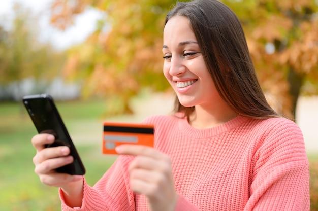 Dame, die online mit einer kreditkarte und einem smartphone kauft, die auf einer couch zu hause sitzen
