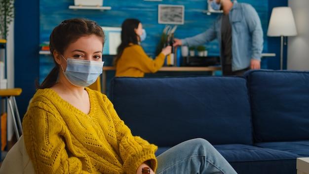 Dame, die sich die kamera anschaut und zeit mit freunden im wohnzimmer verbringt, hält soziale distanzierung mit gesichtsmaske, um die ausbreitung des coronavirus zu verhindern. während des globalen ausbruchs mit bierflasche.