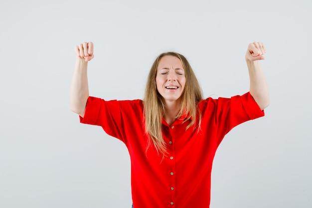 Dame, die siegergeste im roten hemd zeigt und glückselig aussieht.