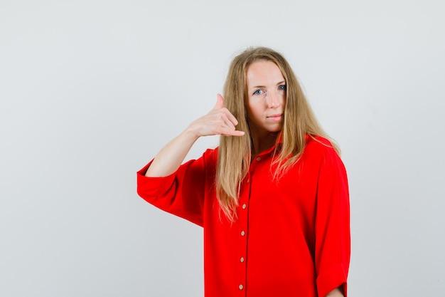 Dame, die telefongeste im roten hemd zeigt und zuversichtlich schaut,