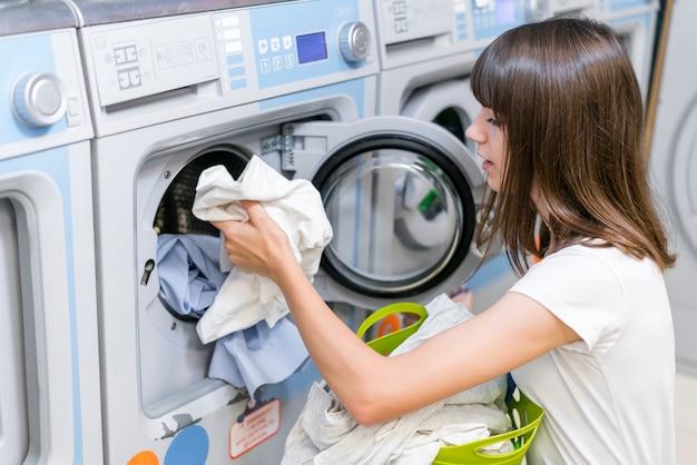Dame, die waschmaschine der wäscherei herausnimmt